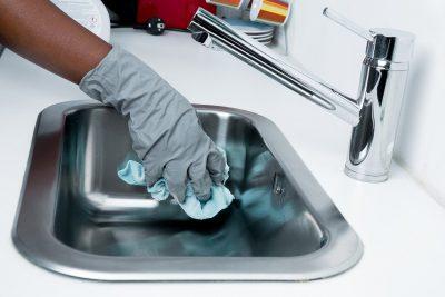 Une personne nettoie un évier